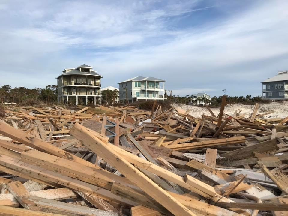 Weeks after Hurricane Michael, a pile of debris on the beach was all that remained of the oceanfront Cape Shoals condominium building on Cape San Blas, while a few homes in the background remained standing through the storm. Photo from David Babcock, Cape San Blas home owner.