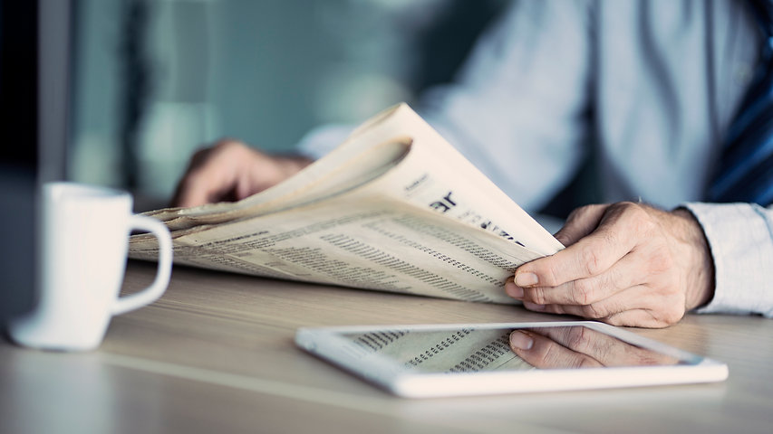 Businessman reading the newspaper on tab