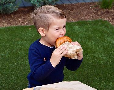 Little boy eating a burger.jpg