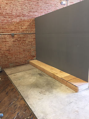 An empty studio space: one wall is exposed brick with a power outlet located halfway up the wall. The otherwall is painted grey and there is a small wooden ledge at the foo of thiswal. The floors are partially concrete an partially antiquewood.