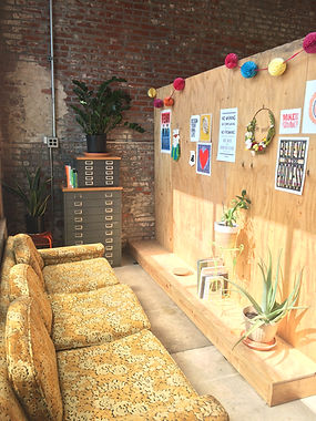 Cherry Pit Collective communal studio lounge, featuring vintage sofa, houseplants and gallery wal of art and print