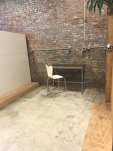 Cherry Pit Collective studo space, historic brick wall, concret floor, moveable drywall wall, and staged with modern office furniure and houseplants