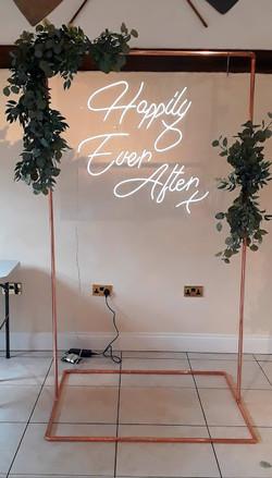 Neon sign, copper arch, faux foliage