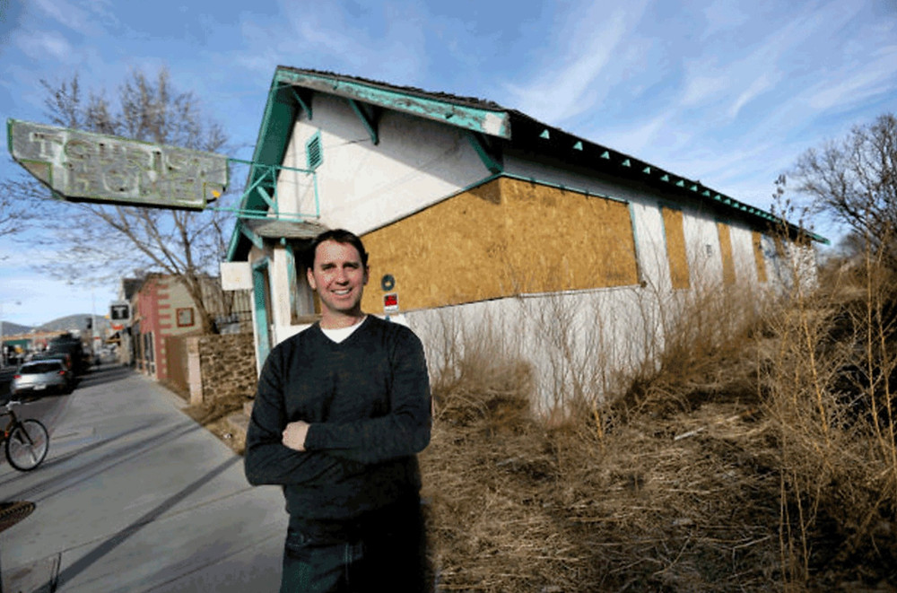 Kevin Heinon stands in front of what was once a derelict building called the Tourist Home which is now renovated and called Tourist Home All Day Cafe
