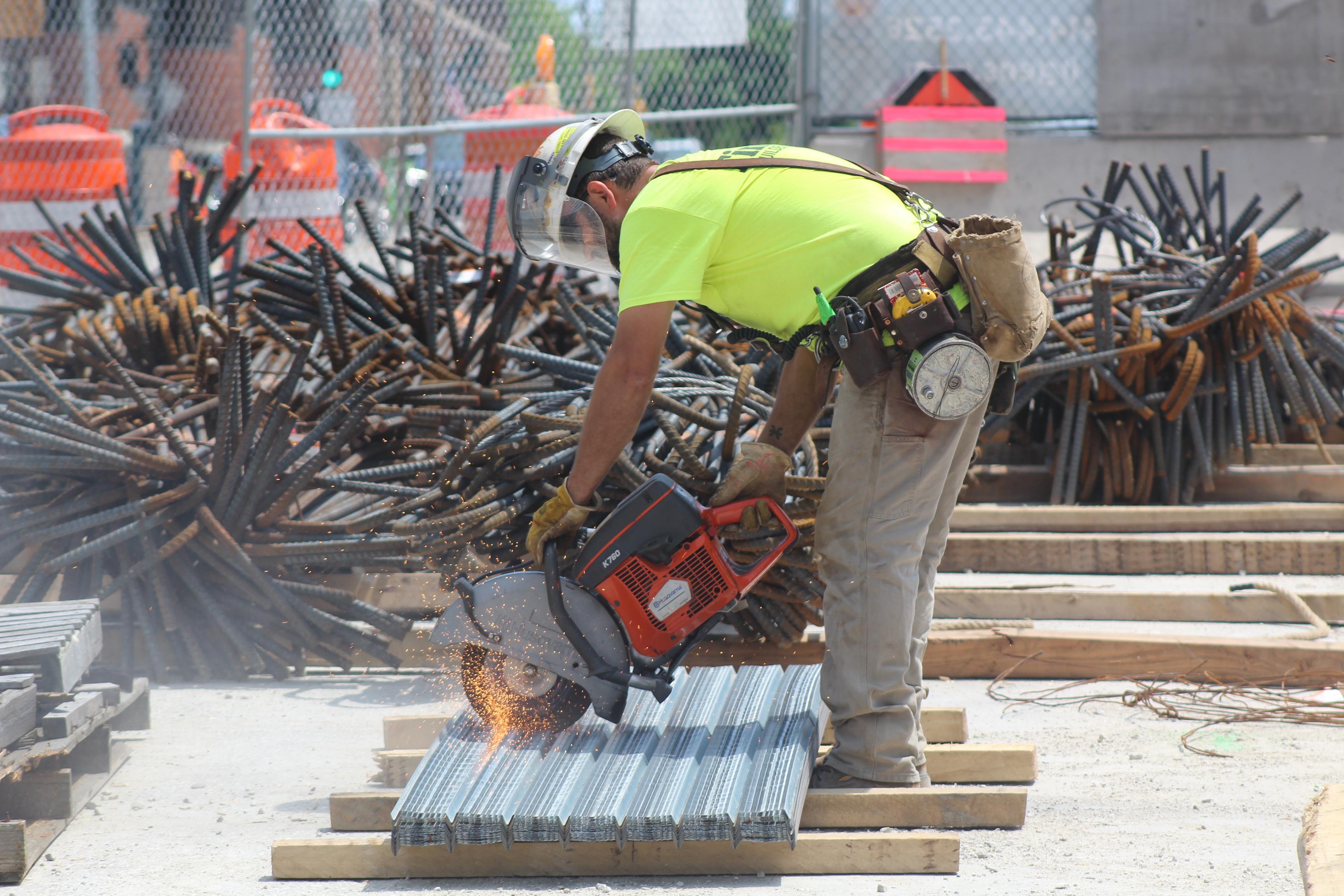 Worker cutting steel.