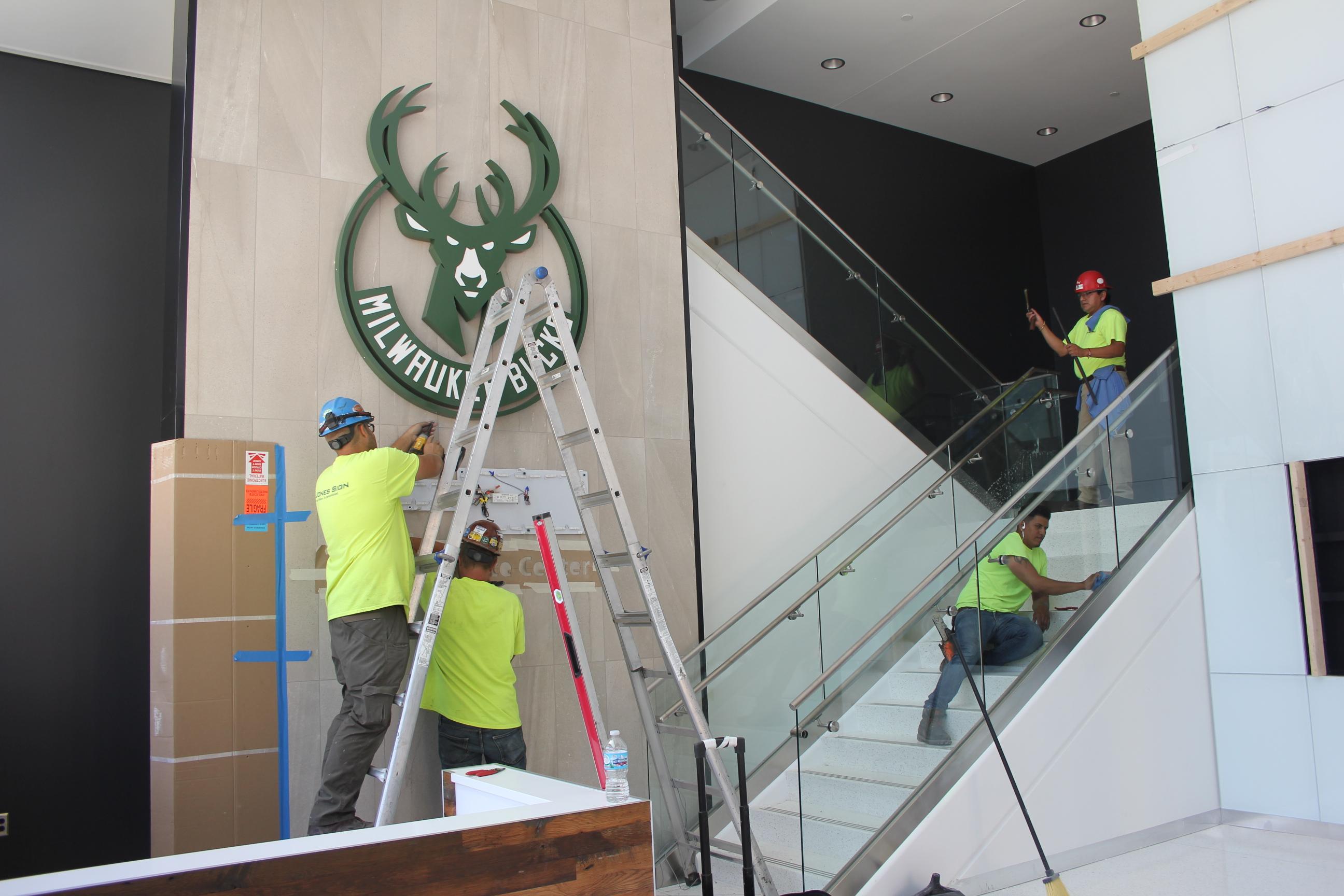 Workers putting on Bucks logo.