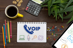 Notebook with a notes VOIP on the office table with tools.jpg Concept with elements of infographics