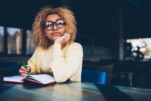 Thoughtful young woman in eyeglasses wri
