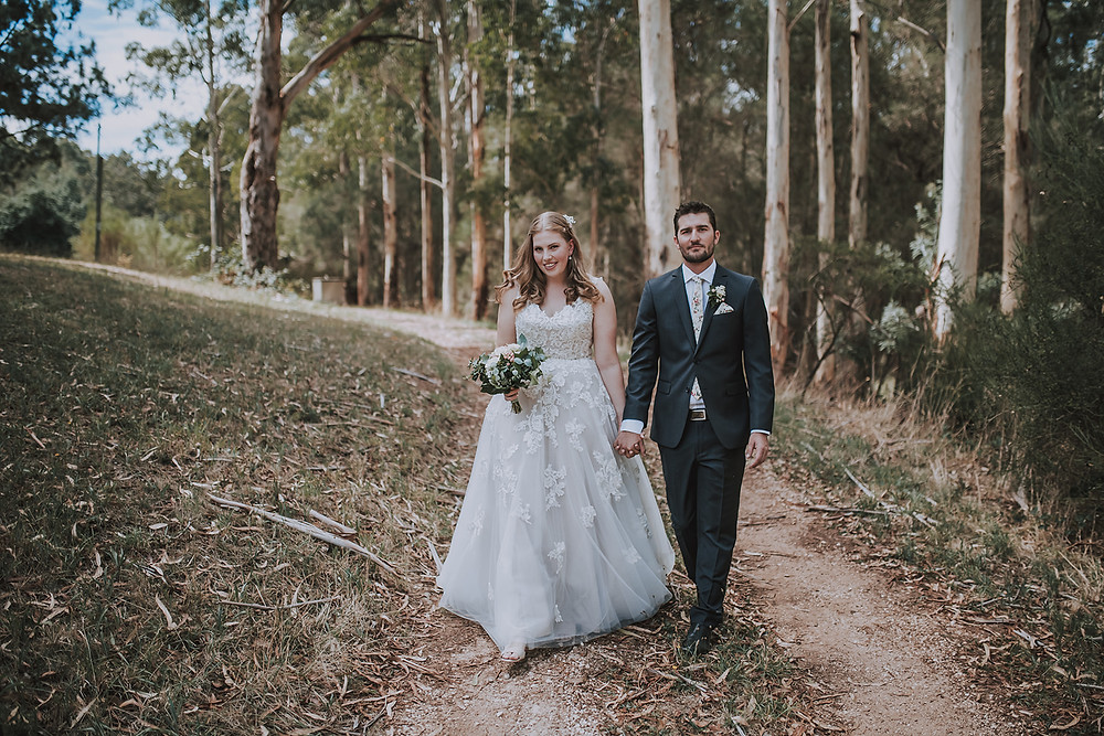 Georgia and Jarrac holding hands and walking along a dirt path at Old Woodhouse Manor