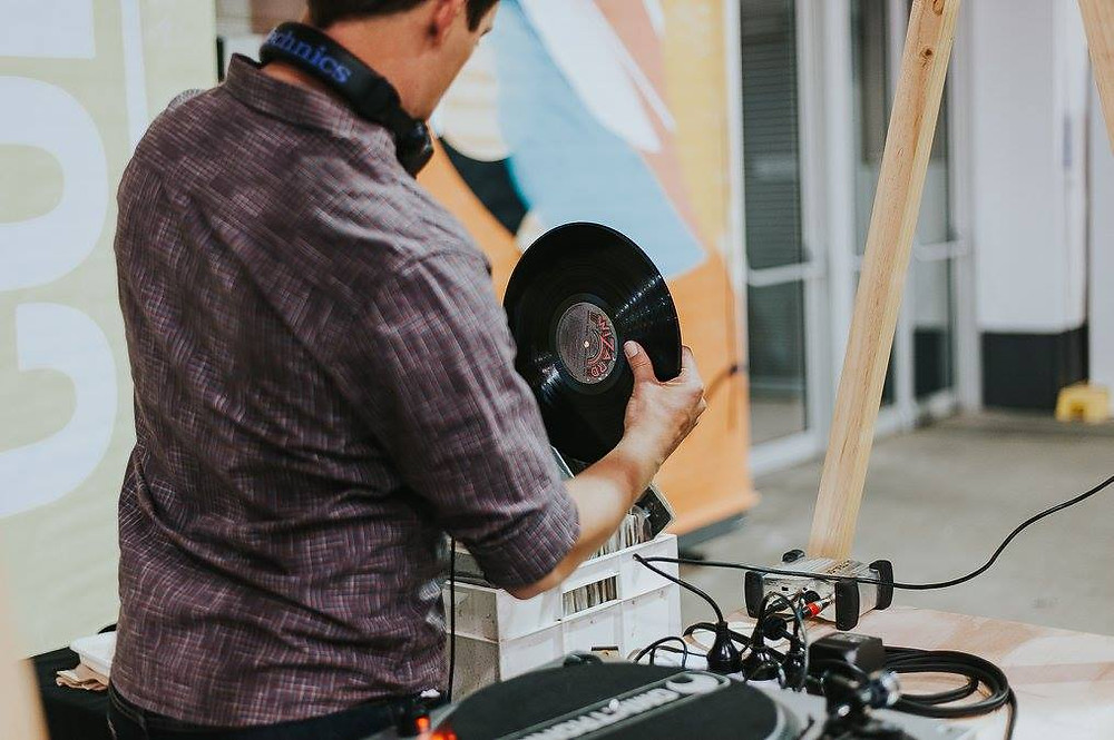 DJ Nick Dawson from Adelaide DJ duo Funk Bros DJs putting a vinyl record back into it's sleeve at Bowerbird Bazaar