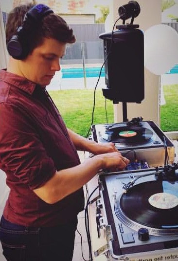 DJ Nick Dawson from Adelaide DJ duo Funk Bros DJs adjusting fader on DJ mixer
