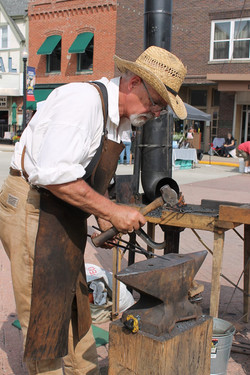 Bill Corey forging at a street fair in h