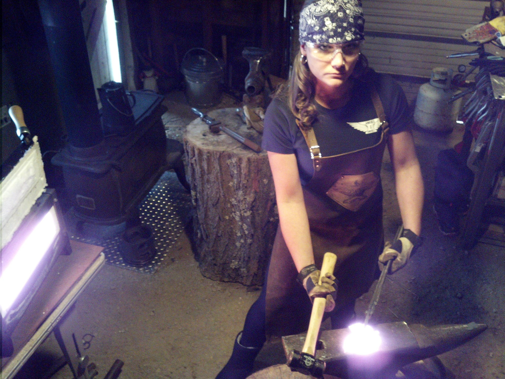 Hitting iron wearing her Forge-Apron