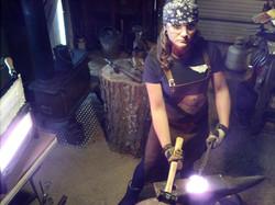 Hitting iron wearing her Forge-Apron