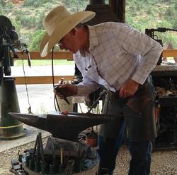 hammering in blacksmiths apron