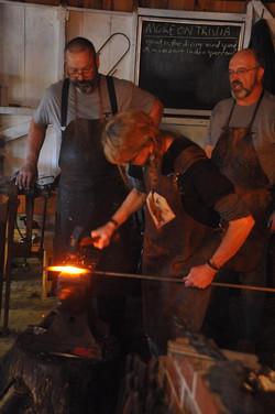 forging in her blacksmith apron