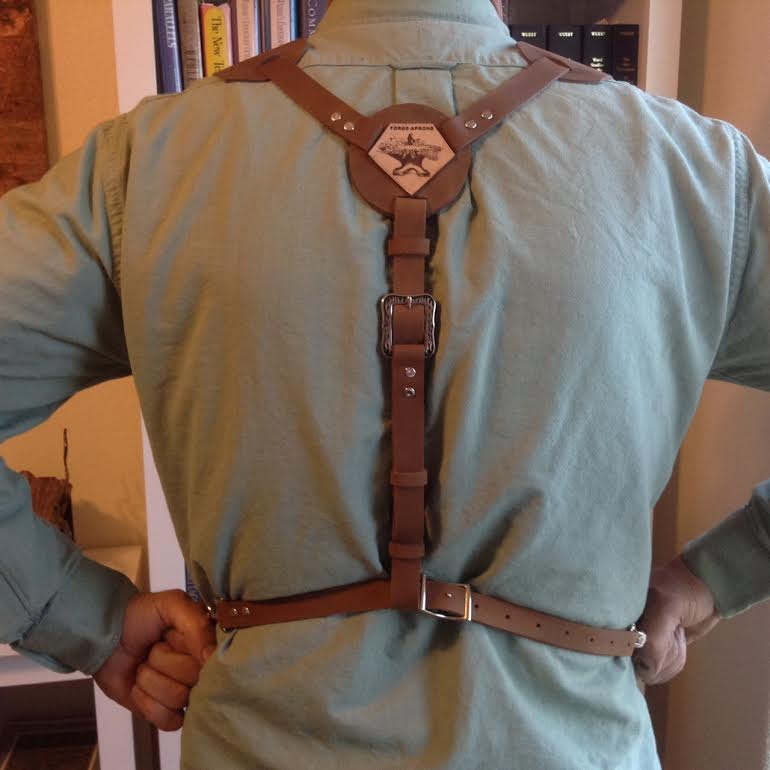 The key to making the Y system work is a snug waist belt as that is what keeps the apron in place. Adjustments are made from the front buckles and the spine strap. Reports are that it is very comfortable and easier to get in and out of. It also holds the leather apron closer to the person's body.