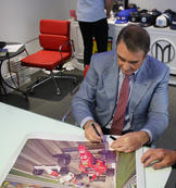 Nigel Mansell signing the print 'Ten-Tenths'