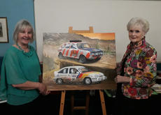 Rally drivers Louise Aitken-Walker and Rosemary Smith with the montage painting of their cars. Charity auction, Brooklands 2019.