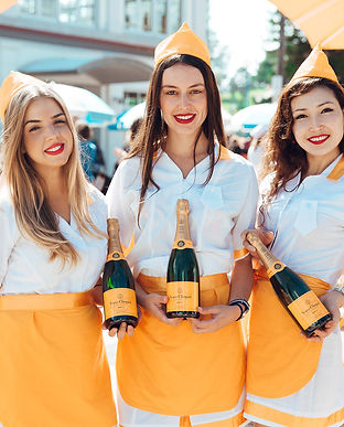 Three smiling waitresses in white drsses with yellow aprons and hats, each holding a bottle of Vueve Cliquot.