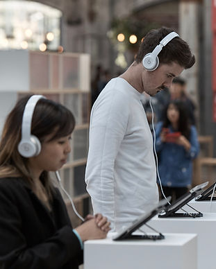 A man in a white long sleeve tee and a woman in a black hit both with white headphones on concentrating on indvidivual ipad screens, whih are placed on white plinths