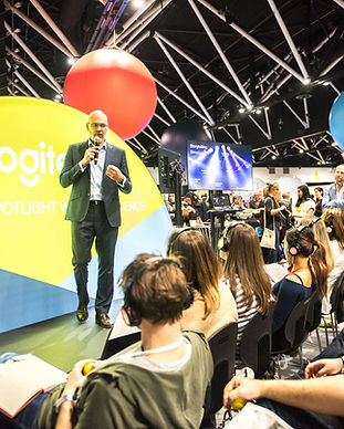 A man in a suit standing on a stage within the TEDxSydney Hub. Behind him is a large yellow semi-circle with the Logitech logo. He is speaking on a microphone to a crowd of seated people wearing black headphones.