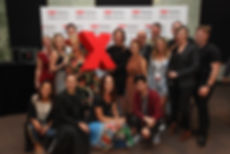 A group photo of the TEDxSydney team of fifteen people standing infrom of the event photo wall with one peson holding a giant red X