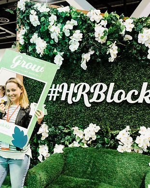 A blonde woman smiling and holding up a cardboard cutout of a polaroid frame with the word grow written on it.In the backgroundis a large green wall covered in grass, leaves and large white flowers with the words #HRBlock in large writing in the centre.