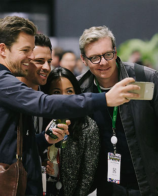 A shot of four people taking a selfie including three men, one wearing black glasses and one woman with black hair. All are smiling.