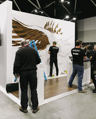 Man standing at a temporary wall painting a large scale mural of a kookaburra, other people standing back watching and talking.