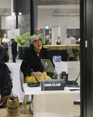 OzHarvest founder Ronni Kahn laughing whilst in a radio both wearing headphones