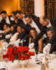 Smiling people in formal dress sitting at a long table with red floral centrepieces. Behind them are waiters in white tie dress leaning over them with their meals.
