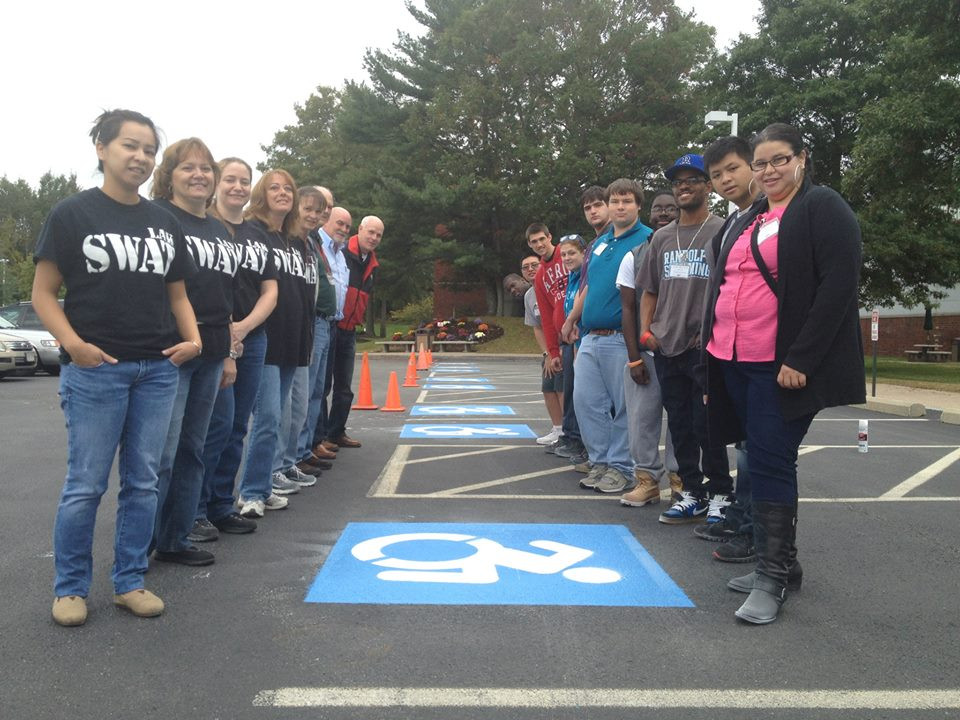 People standing around a parking space with replaced logo