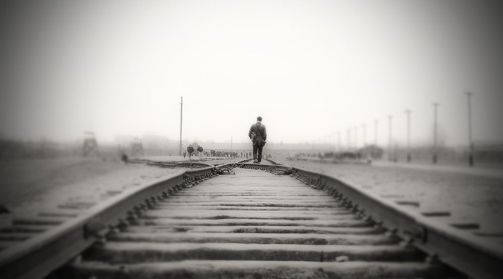 A man walking on the railway line at Auschwitz concentration camp