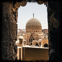 dome-of-a-mosque-through-the-arch-of-a-minaret-in-the-city-of-the-dead-in-cairo-egypt-(cre