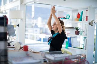 Female executive doing yoga on desk in o
