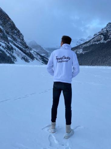 @gjhoogteijling in een wit met zwarte TravelDudes hoodie in de sneeuw in Canada