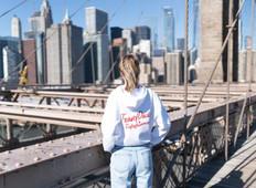 @alidahoogteyling met haar wit met rode TravelDudes hoodie op de Brooklyn bridge in New York