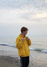 @karel12345678 met zijn geel zwarte hoodie op het strand