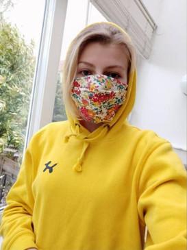 @yziparis met gele TravelDudes hoodie en mondkapje met bloemen
