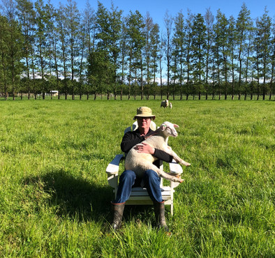 A man and his lamb in a paddock.