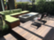 A wooden deck cleaned, with green cushioned sofa and to patio chairs