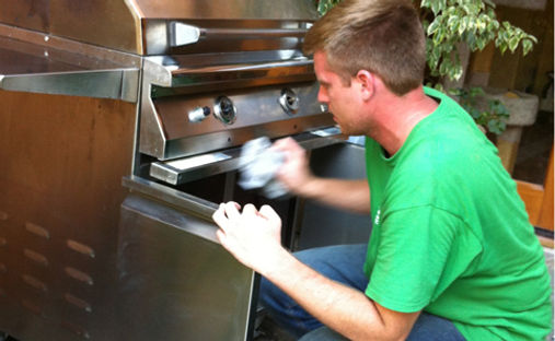 A worker kneels in front of a stainless steel grill, quickly polishing the exterior