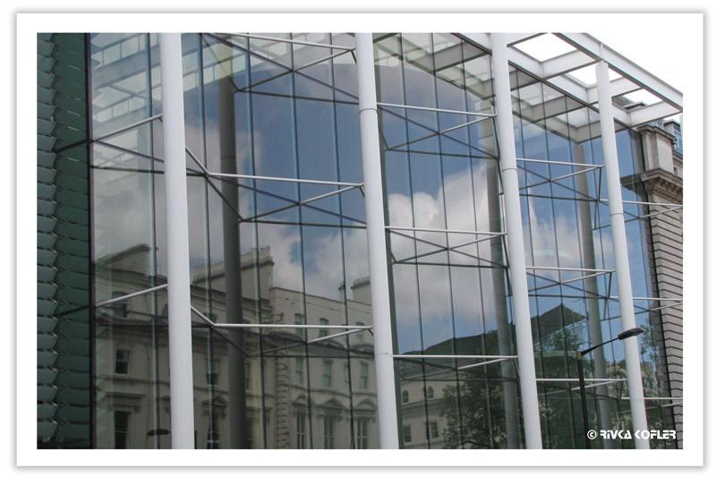 השתקפות בניין ישן בזכוכיות בניין מודרני