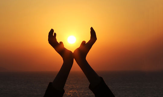 man hands holding the sun at sunrise wid