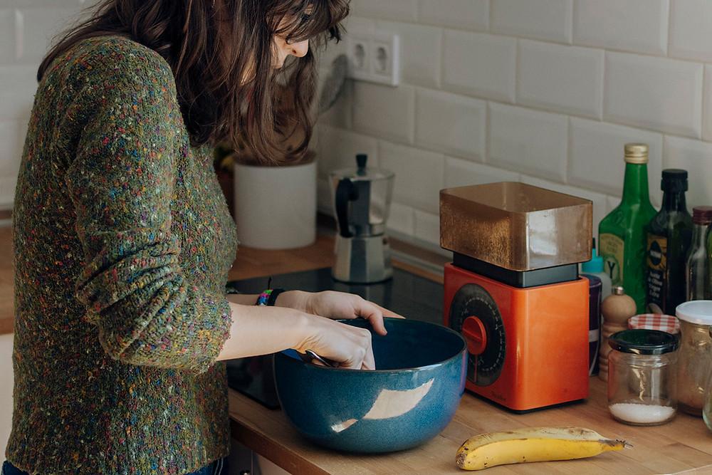 Mujer con jersey verde cocinando en un bowl azul un bizcocho de plátano.