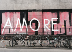 bicycles leaned on a mural wall that says Amore