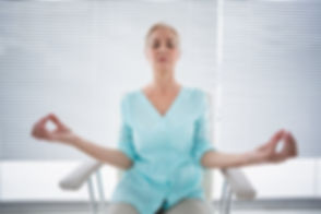 Senior woman doing yoga on chair at fitness studio.jpg