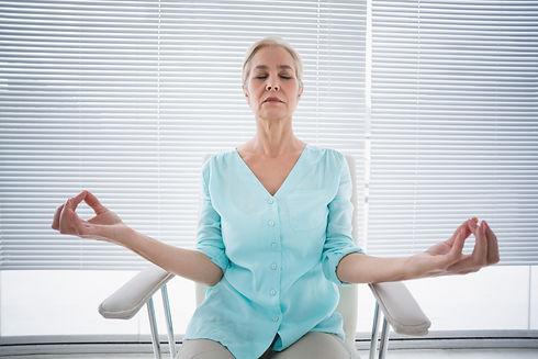 Senior woman doing yoga on chair at fitness studio.jpg