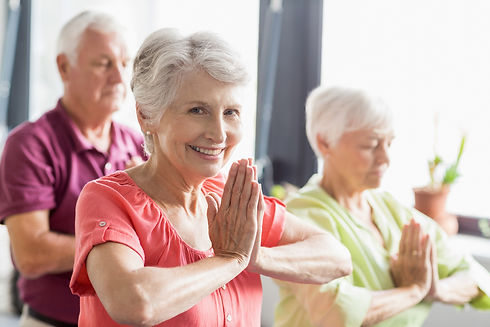 Seniors doing yoga with closed eyes in a retirement home.jpg